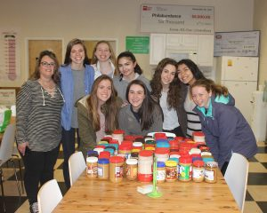 Students from the Friends' Central's Service Committee holding bottles of peanut butter at the Philabundance Hunger Relief Center